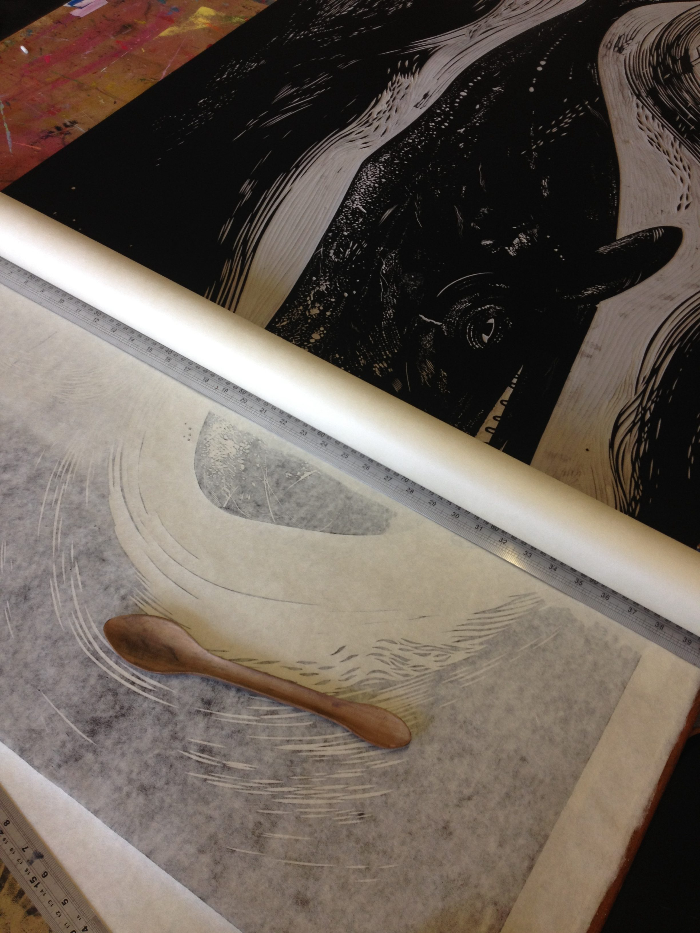 Hand printing linocut with a wooden spoon