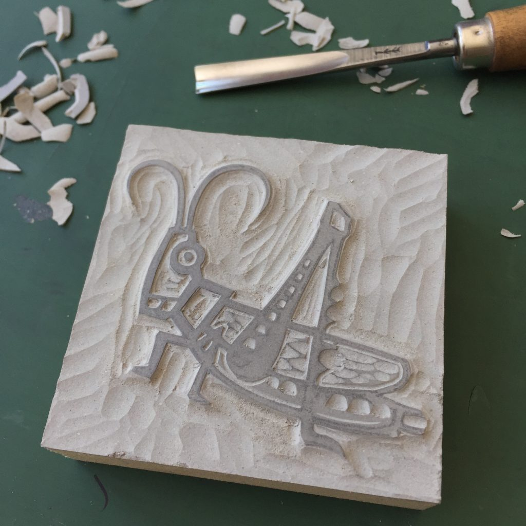 Linocut block of a cricket